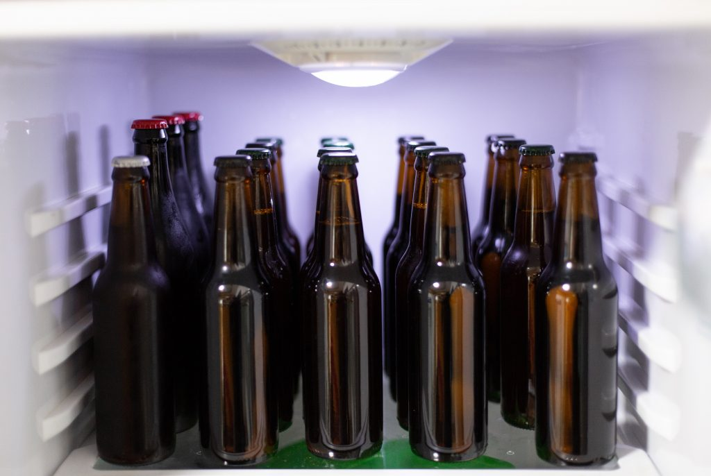 Bilde fra innsiden av et kjøleskap. Vi ser mange brune ølflasker.