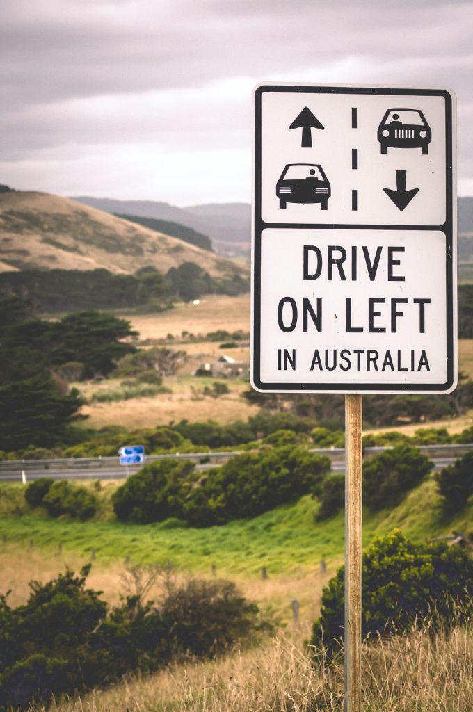 """En vei i Australia med skiltet """"Drive on left in Australia""""."""