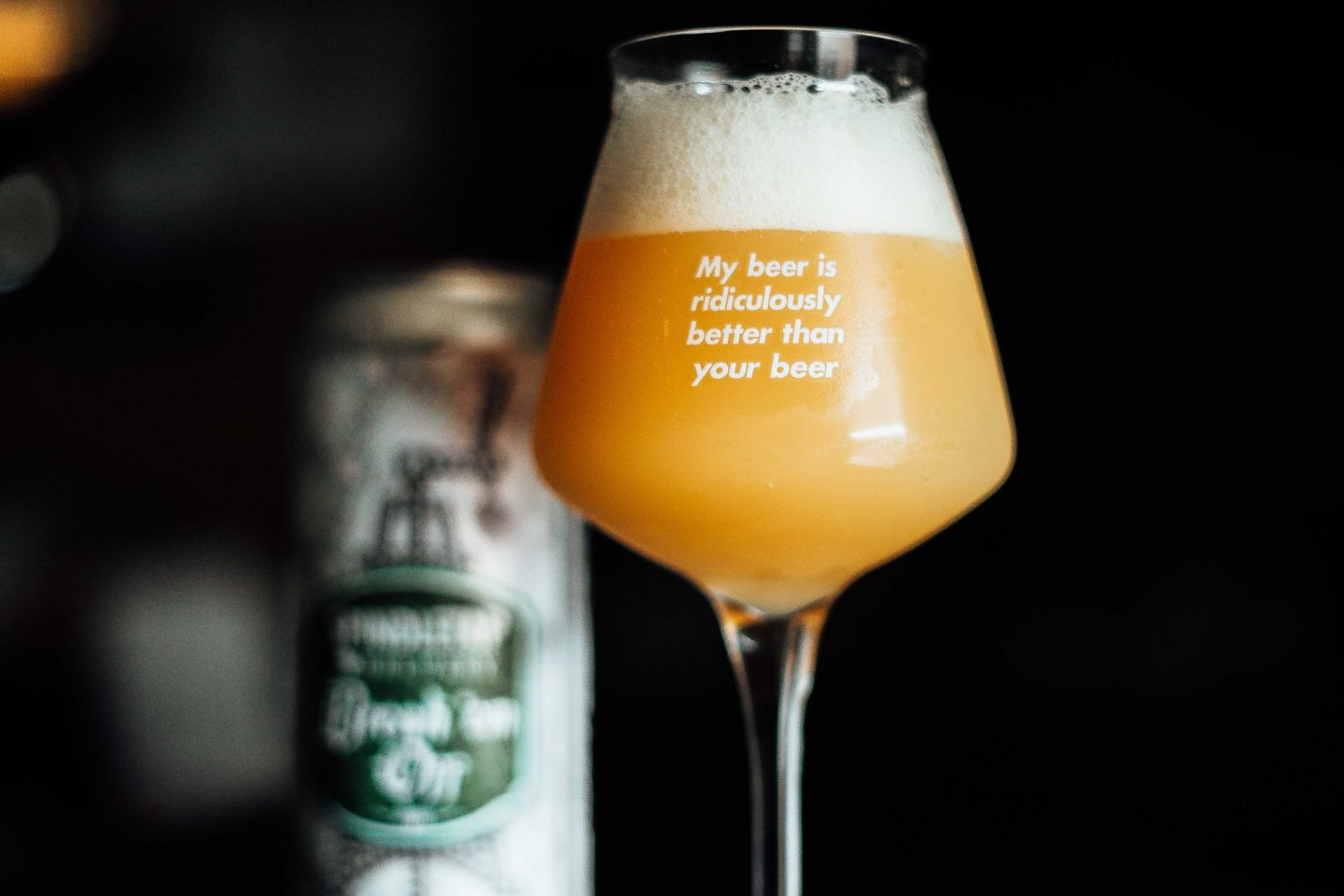 "Et teku-ølglass med teksten ""My beer is ridiculously better than your beer"". Ølet er en tåkete og fyldig NEIPA. Boksen er ""blurry"" i bakgrunnen."
