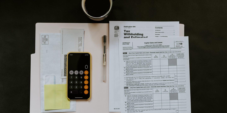 Bilde av en mobil med kalkulator oppe og ark med skatteoppgjør