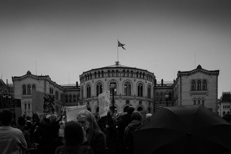 Et bilde av det norske stortinget i Oslo i svart-hvitt med en rekke demonstranter foran.