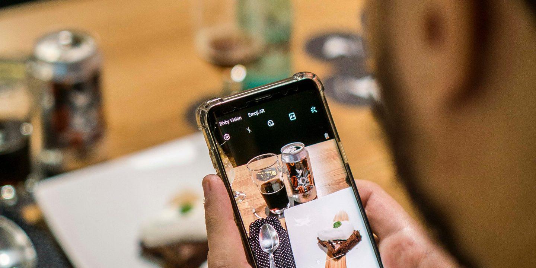En person tar bilde av mat og et glass med øl og ølboksen.