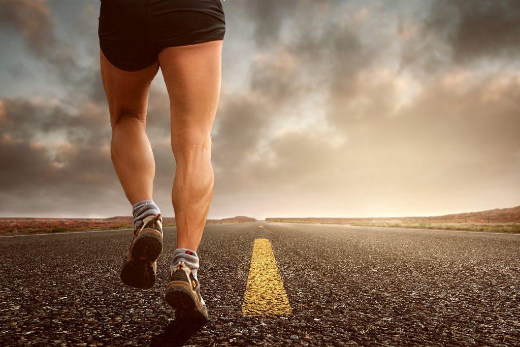 Vi ser beina bakfra til en mann som jobber på en rett asfaltveien.