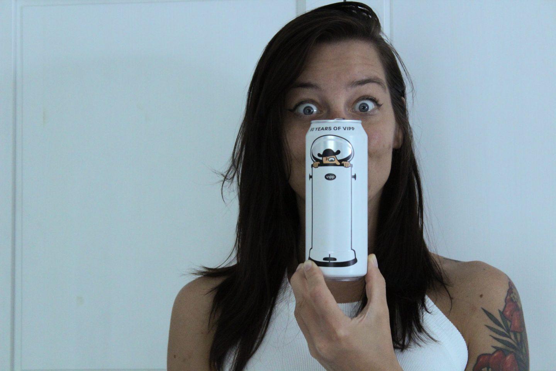 En dame med store øyne holder en boks med øl foran ansiktet.