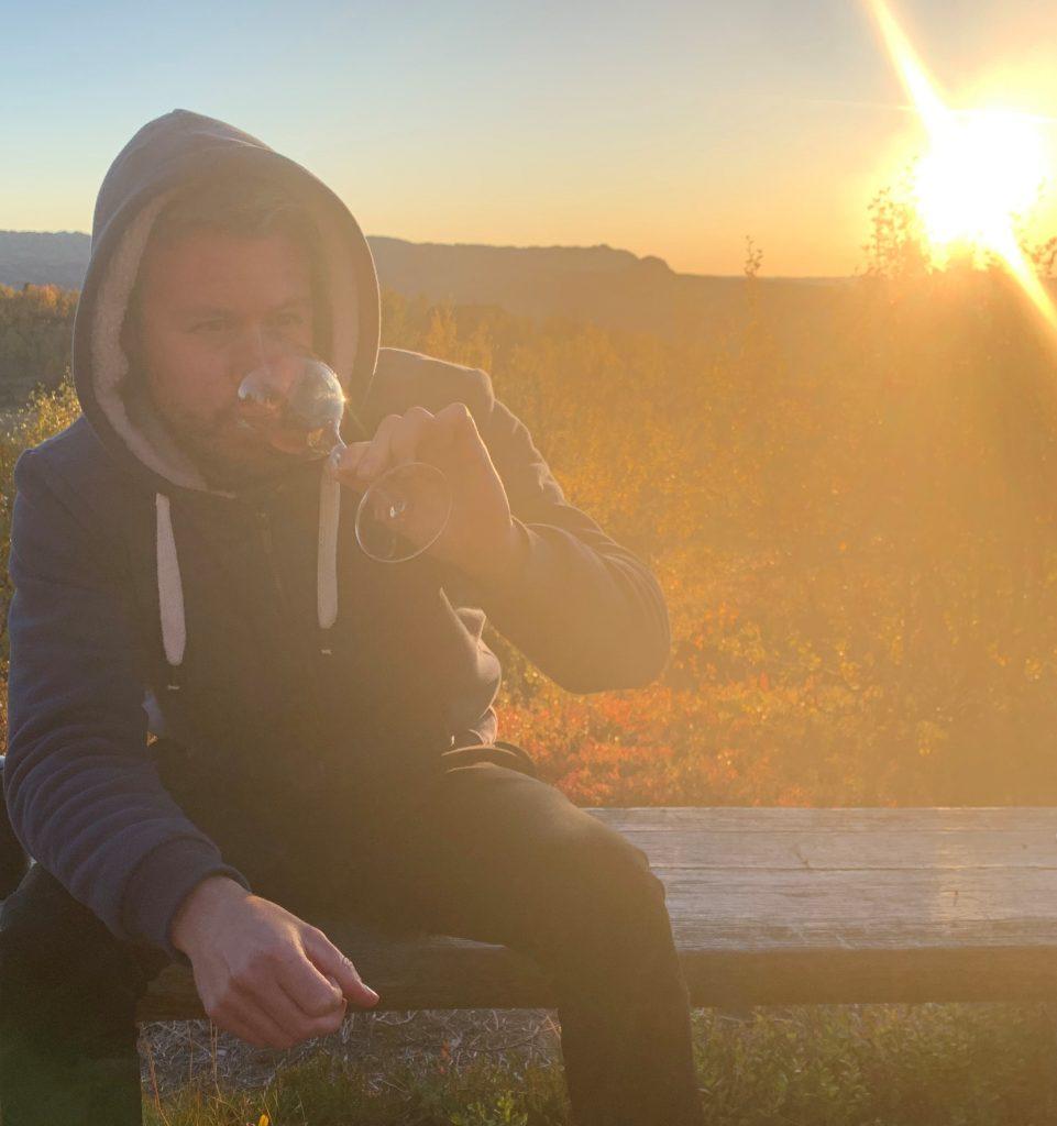 Bilde av meg i solnedgang med et vinglass i hånda