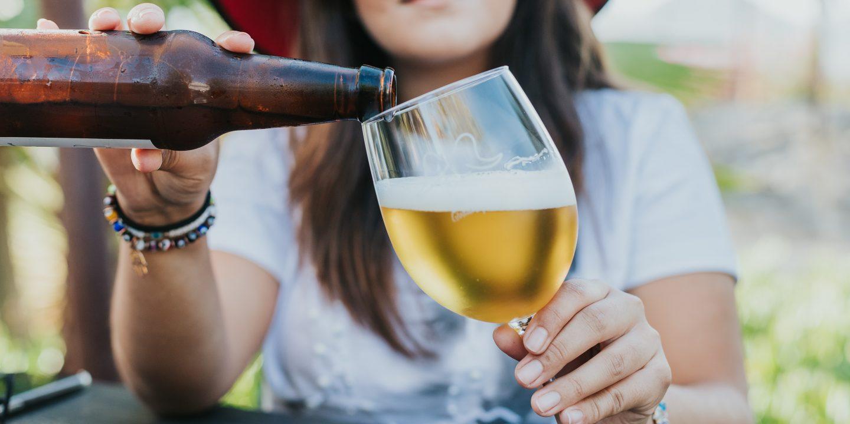 En kvinne med hatt som fyller øl fra en brun flaske i et glass med stett.