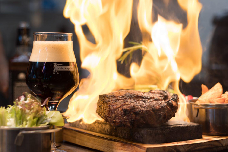 Et glass med mørkt øl i til venstre på bordet. En biff i midten og flamme bak.