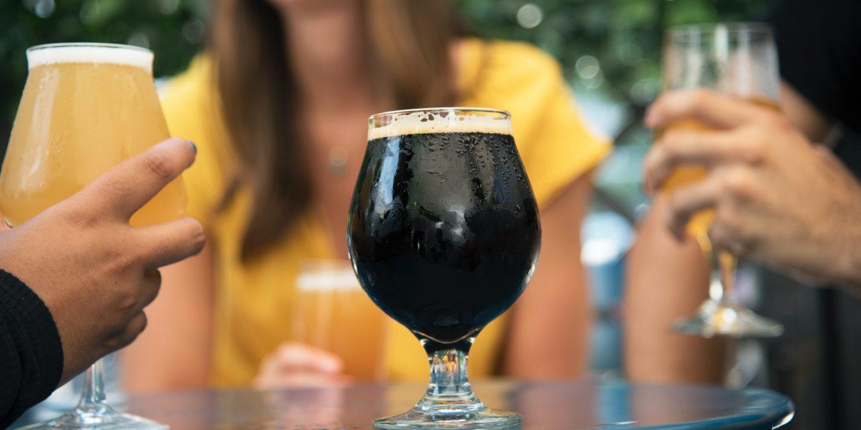 Mange ølglass på et bord med folk rundt. Det midterste glasset er et svart øl.