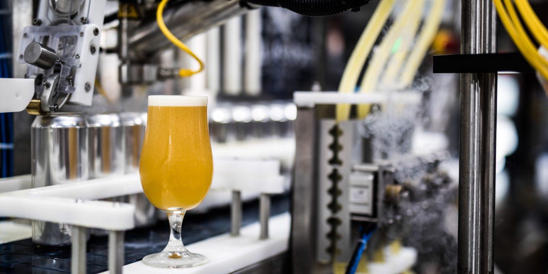 Bilde av et brusende glass med lyst øl inne på et bryggeri.