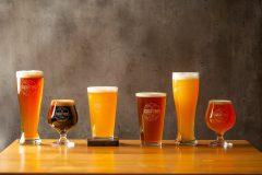 Flere ulike øl i ulike farger og glass på en benk.