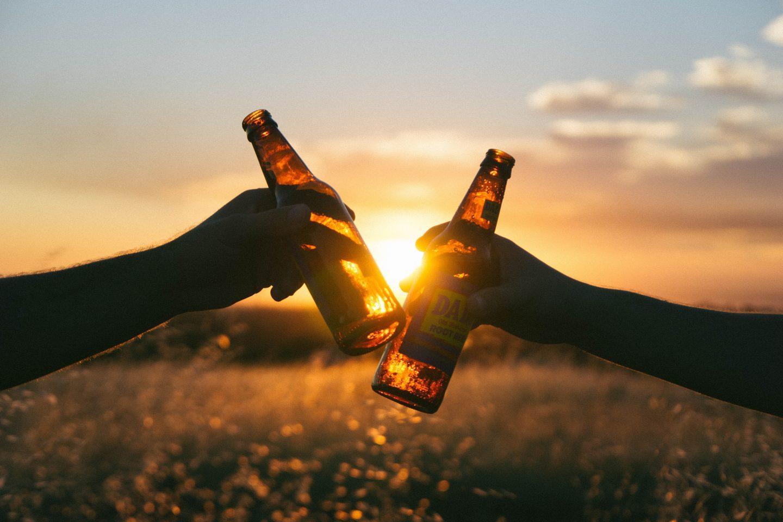 To som skåler med to ølflasker i solnedgang.