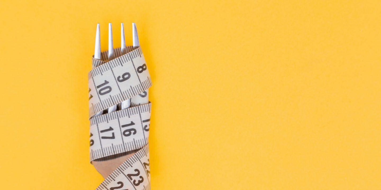 Bilde av et målebånd tvinnet rundt en gaffel. Gul bakgrunn.