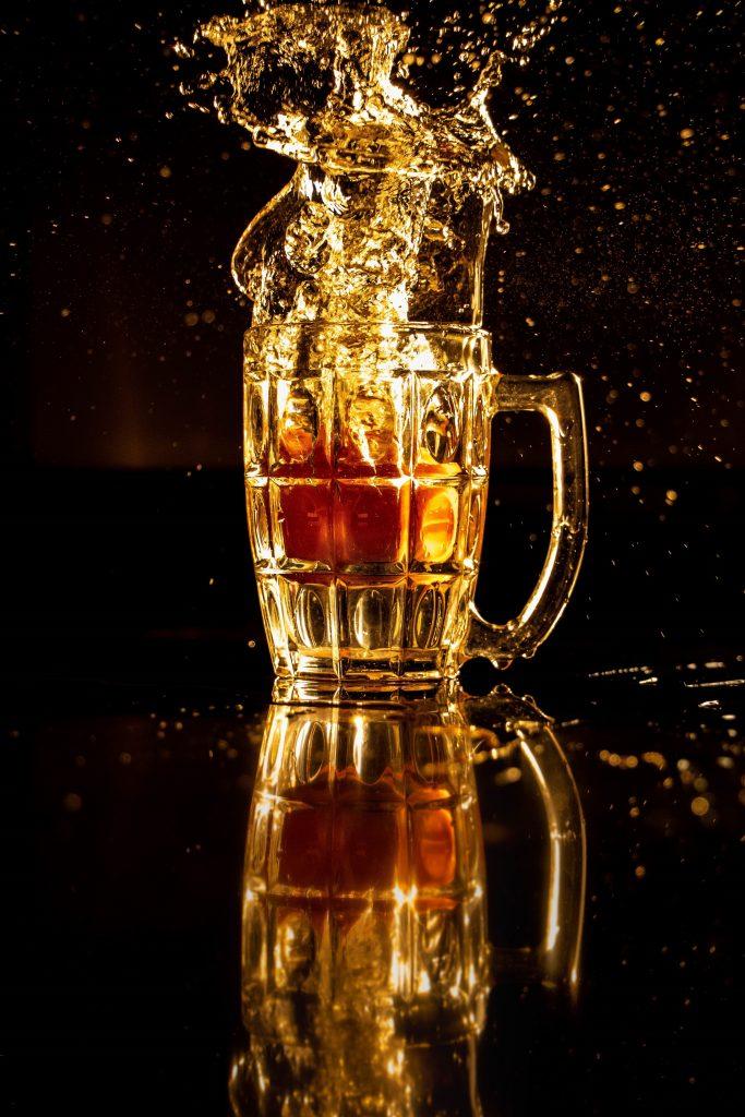 Øl som splæsjer i et Pilsnerglass.