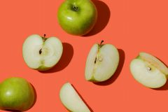 Grønne epler på en rød flate. Noen er hele og andre kuttet opp.
