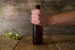 En fyr holder en flaske med øl. Et glass med humleblomster i bakgrunnen.