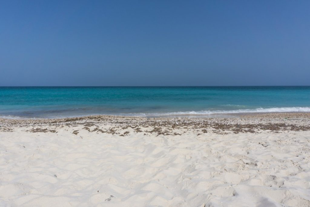 Secret beach in Oman. The picture shows beautiful white sands and turquoise water.
