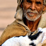 Bedouin man carrying lamb