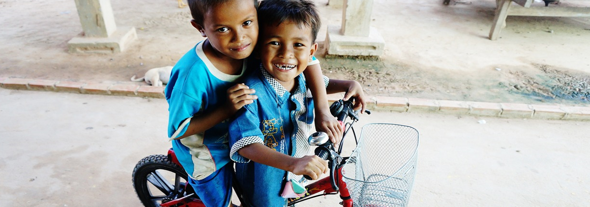 two smiling children on a bicycle