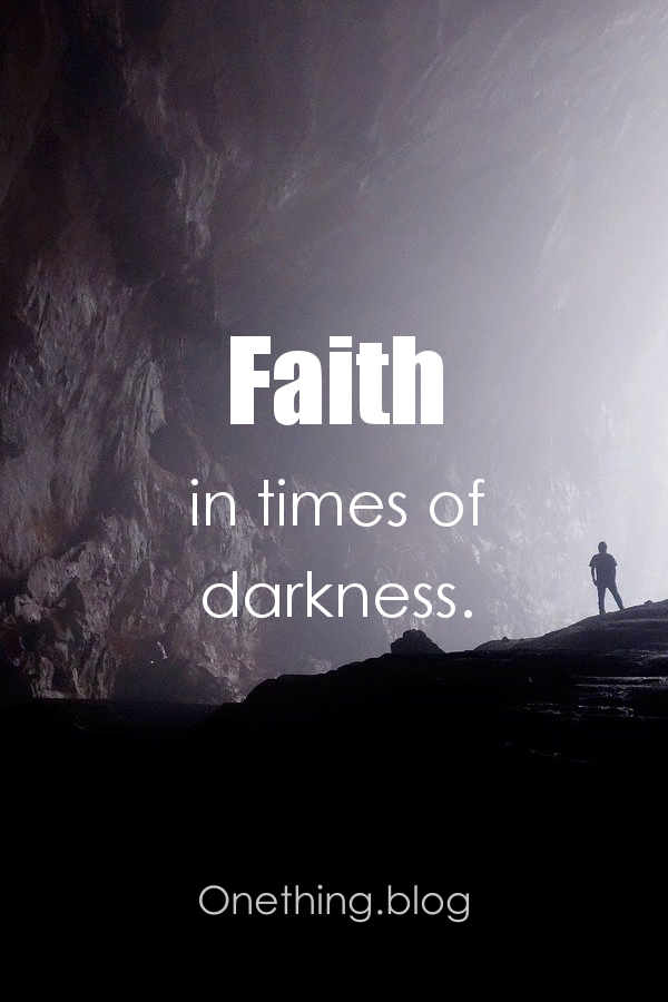 Man standing in a cave. Faith in times of darkness