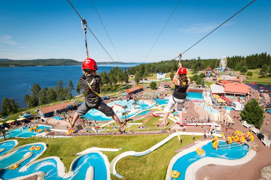 To barn kjører zipline ned mot badelandet i Leksand Sommarland i Dalarna