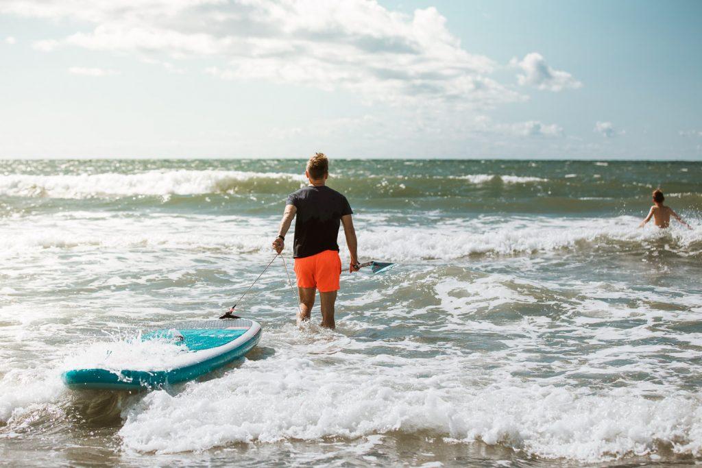 En mann skal ut og surfe i bølgene i Halland