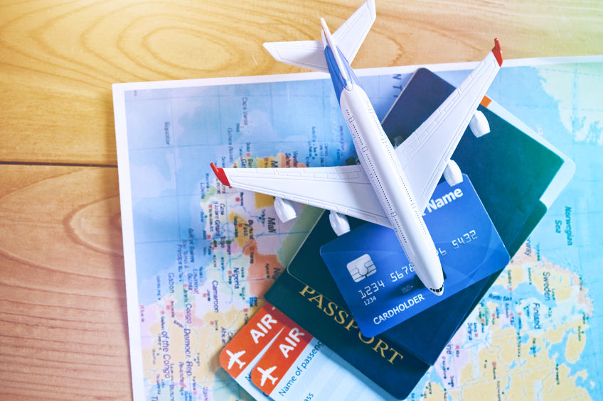Air tickets, passports and credit card on world map. Online ticket booking and holiday planning concept