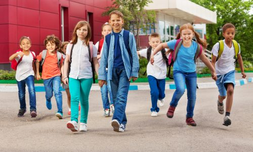 Children with rucksacks near school building walking holding hands during summer day time