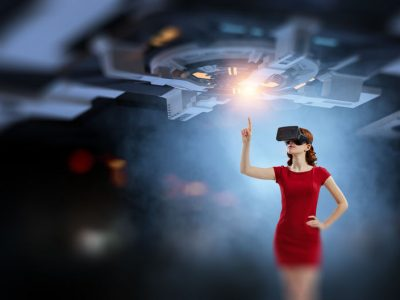Young woman in a red dress in VR headset on abstract technology background. Mixed media