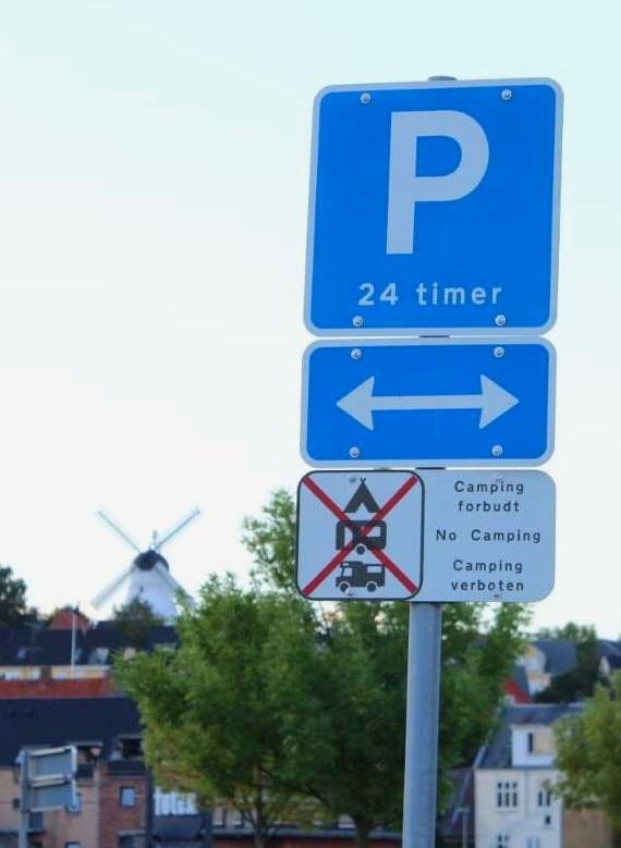 """Skiltet her er et eksempel fra en kommunes måde at adfærdsregulere autocampister på. Det øverste skilt tillader ifølge afmærkningsbekendtgørelsen parkering i 24 timer og tillader dermed overnatning for autocampere og campervans, mens skiltet i midten viser hvilke parkeringsbåse, der er tale om. Det nederste skilt ulovliggør dog umiddelbart overnatning for autocampere og campervans. Skiltet er dog ikke umiddelbart beskrevet i hverken afmærkningsbekendtgørelsens § 15 eller § 17. Skiltet hører formentligt derfor ikke ind under færdselsloven, men retter sig alene mod aktiviteten """"campering"""", og dermed ikke mod hvilken type transportmidler der må parkere 24 timer i p-båsene. Autocampere og campervans må derfor gerne overnatte i p-båsene. De må bare ikke campere. Foto: Kim Basse"""