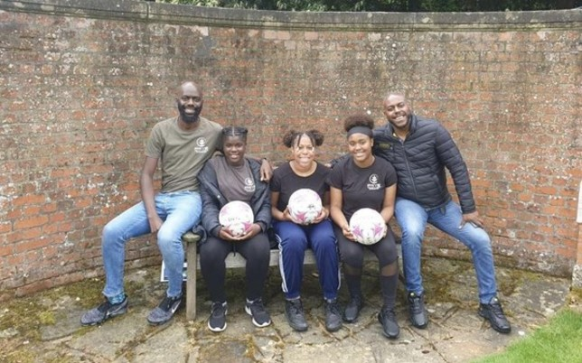 David, Wayne and Kids sitting holding footballs in their hands