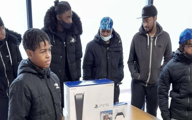 youngs boys standing around a table with ps5h