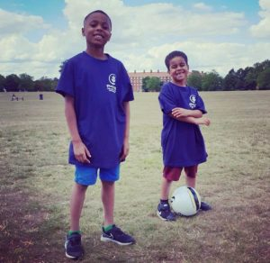 2 young boys standing with a football