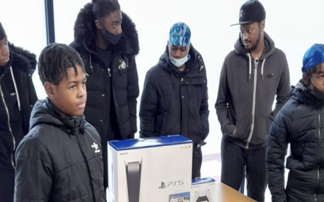 boys standing around a table with PS5