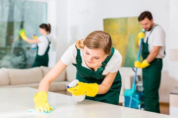 Rengøring af bord af kvinde med handsker