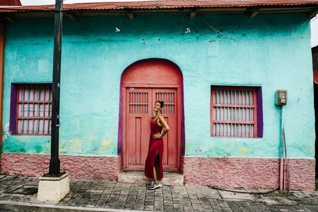 vrouw voor gekleurde huisjes in Flores Guatemala