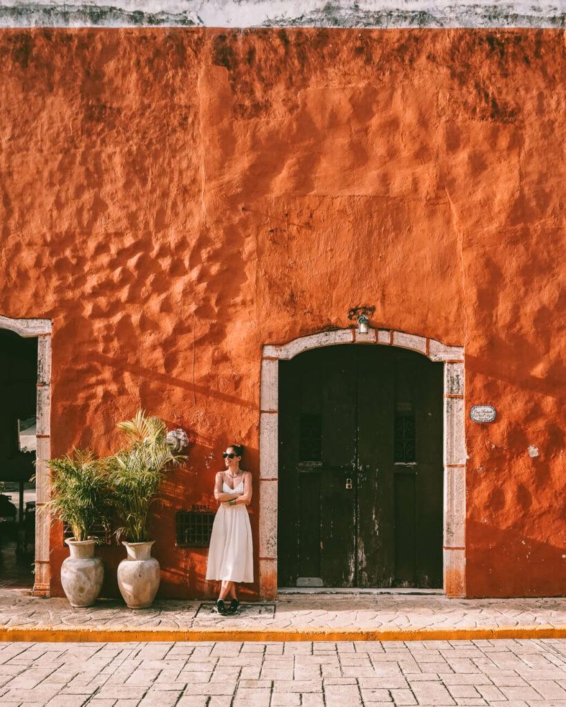 Deborah voor oranje gekleurd huis in Valladolid in Mexico