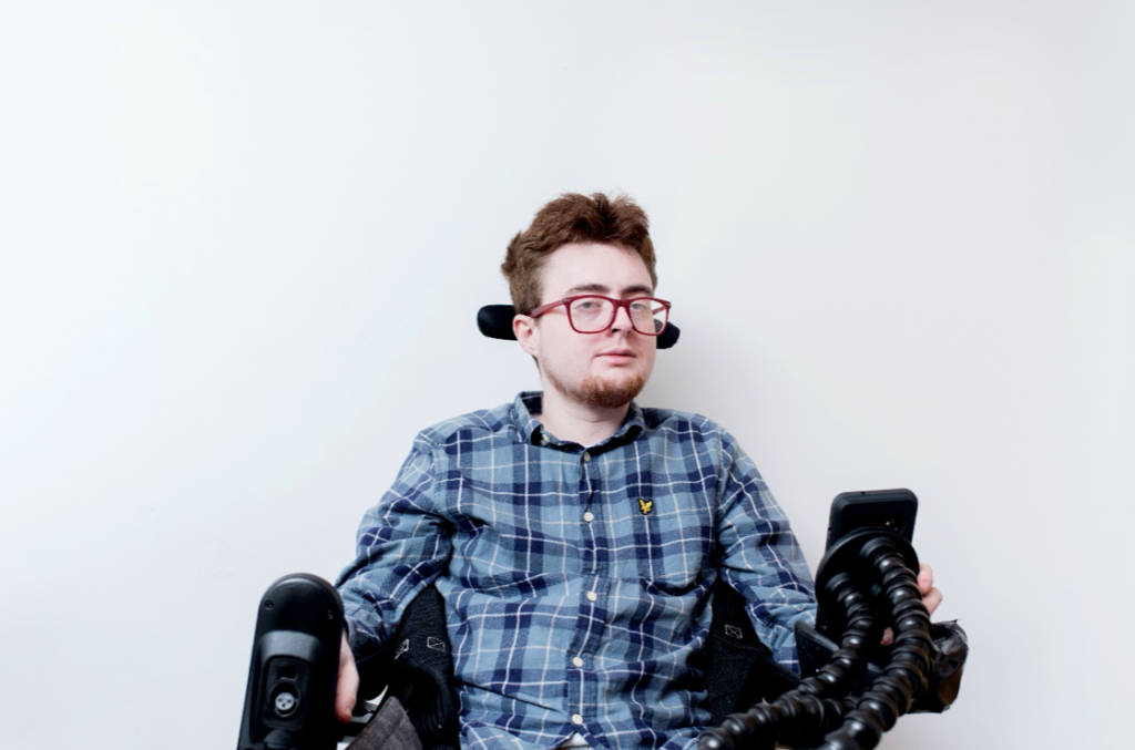 Jamie Hale, co-CEO, in a blue plaid shirt, in a black electric wheelchair. They have dark red hair and beard, and bright red glasses