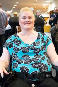 A photo of Kerry Thompson, blonde in a blue and black flowery top and a black electric wheelchair
