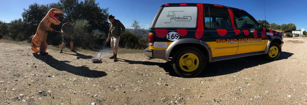 Car painted yellow orange and black, with Team DMD Pathfinders written on the side in a desert looking environment with two men behind wrangling an inflatable dinosaur, taken at the Gib or Bust fundraising event