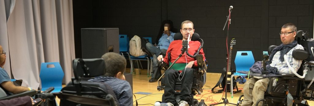 CEO, Jon Rey-Hastie presents to a room. He is in an electric wheelchair and wearing a red jumper