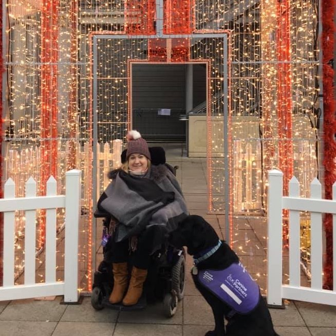 White woman with blonde hair and brown eyes in a wheelchair, wearing a grey coat and brown bobble hat posing with a large black dog in front of white fairy lights.