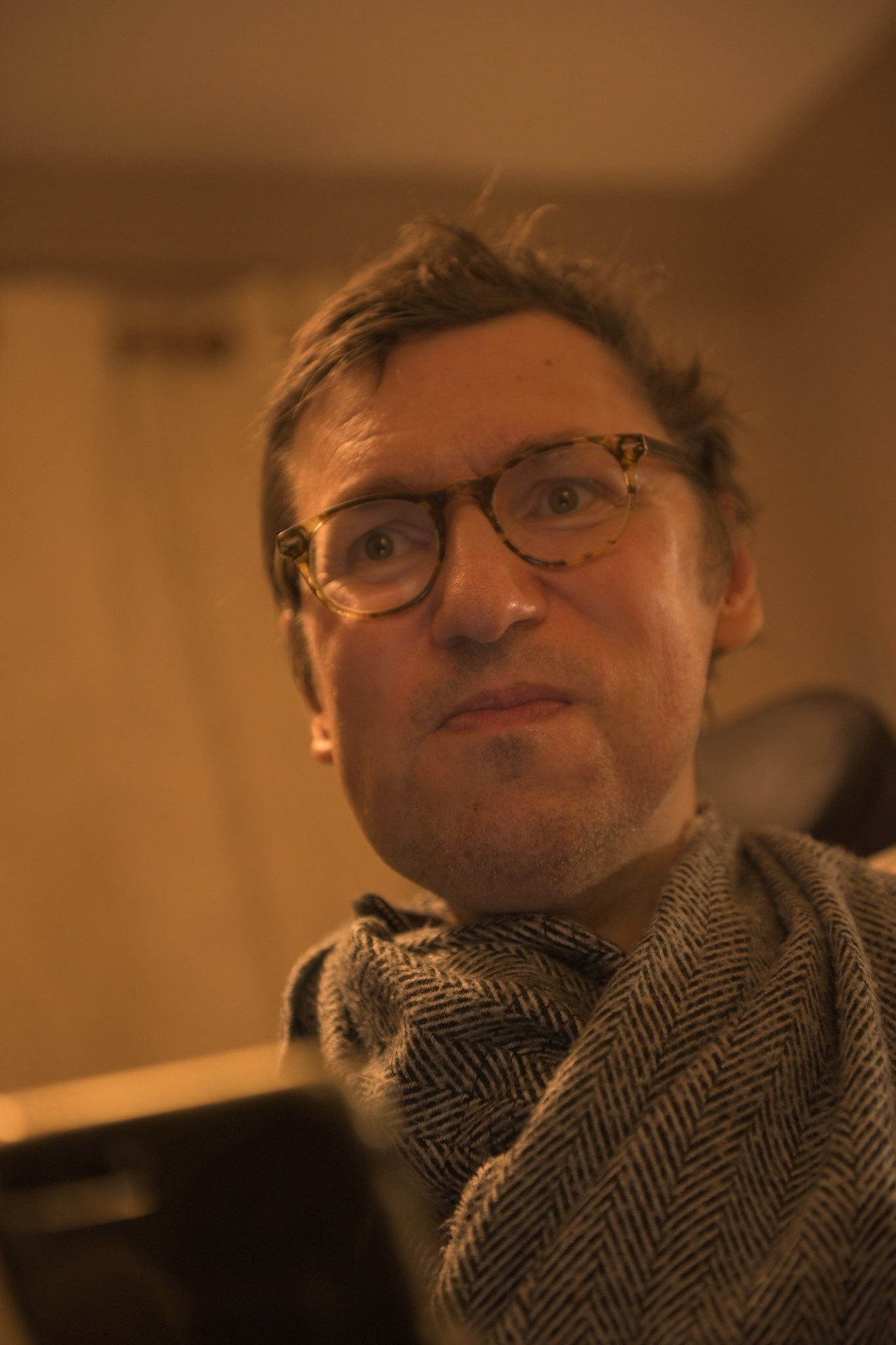 Brown haired, brown eyed male wheelchair user with glasses, wearing patterned grey scarf in lounge. Beige lighting.
