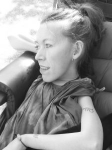 Black and white photo of the head and shoulders of a white woman sat in a chair looking to the left. Her hair in a high ponytail