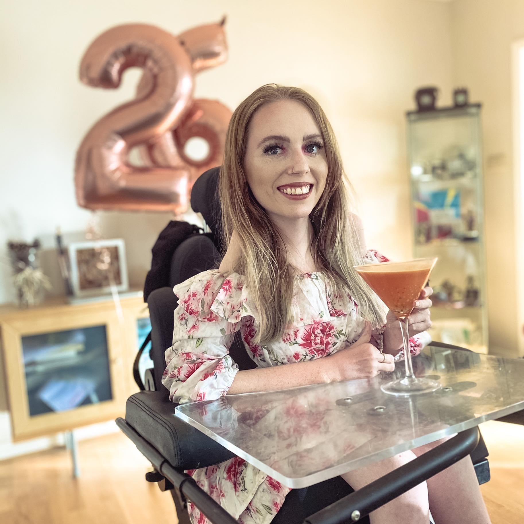 Young woman with light shoulder length hair sat in a powerchair wearing a white dress with pink flower print. Holding a martini glass filled with a red liquid on a clear tray. The background is a light living room with 26 shaped pink balloons.