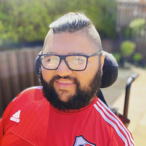 Head and shoulders of a young man with full beard and mustache with short dark hair and black rimmed glasses. Sat in a wheelchair in the garden wearing a red football shirt