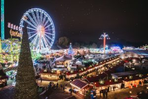 Christmas market lit up at night with giant ferris wheel and Christmas tree.
