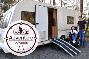 Karla, sat in powerchair with Stephen, stood, outside a caravan with ramp at open door. Adventure wheels logo on left of picture.