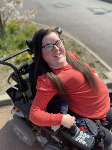 Kate wearing a red jumper with long brown hair in an electric wheelchair