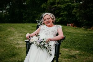 Suzanne with blonde hair in a black wheelchair wearing a wedding dress