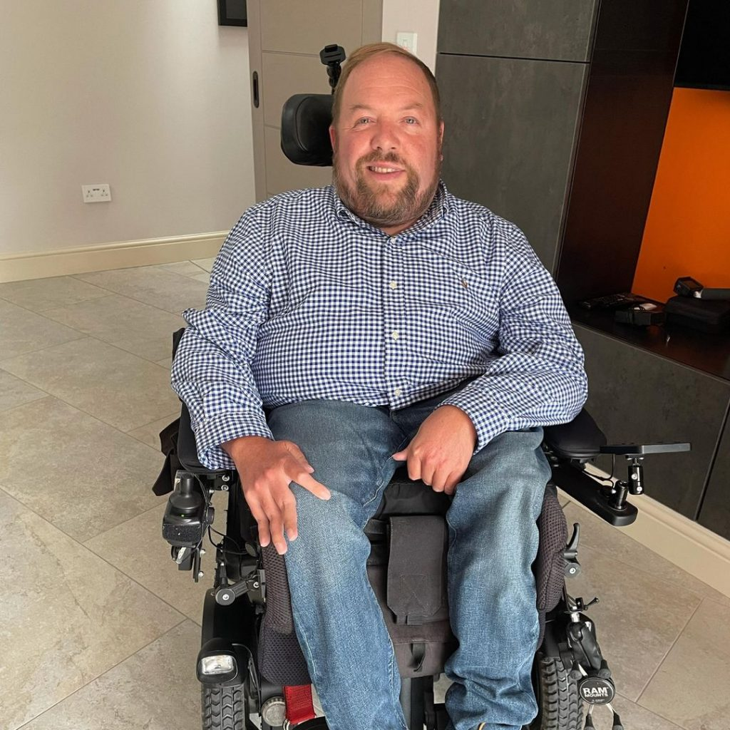 A man with brown hair sitting in a powered wheelchair in a house